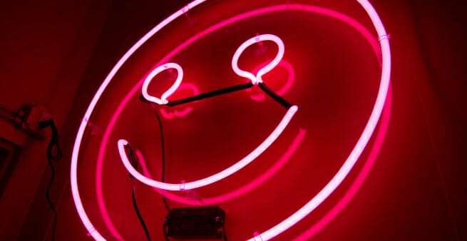 neon smiley face as proxy for catchy headlines evoking emotion